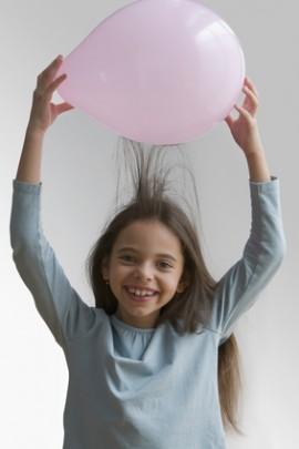 Hispanic girl creating static in hair with balloon