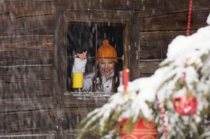 Junge Frau schaut auf Weihnachtsbaum, lächelnd